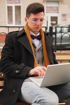Affari e libertà. uomo d'affari moderno, tastiera del computer portatile con un computer portatile su una panchina e lavorando,