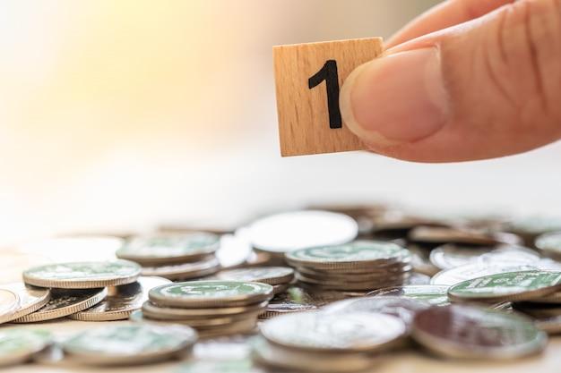 Affari, finanza, pianificazione del denaro e concetto di risparmio. la fine del blocco di legno di numero 1 tiene dall'uomo consegna la pila e il mucchio delle monete d'argento e copia lo spazio.