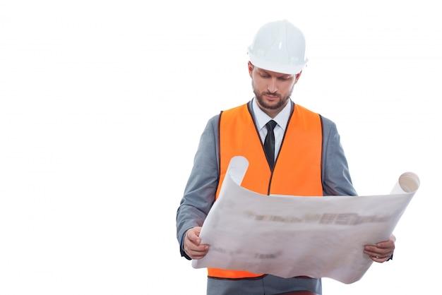 Affari in costruzione. costruttore maschio professionista in una maglia e un casco di sicurezza che lavorano ad un progetto di costruzione