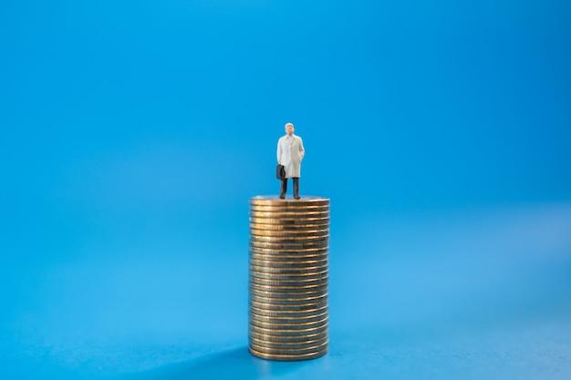 Affari, investimenti in denaro e concetto di pianificazione. chiuda su della figura miniatura della gente dell'uomo d'affari con la borsa