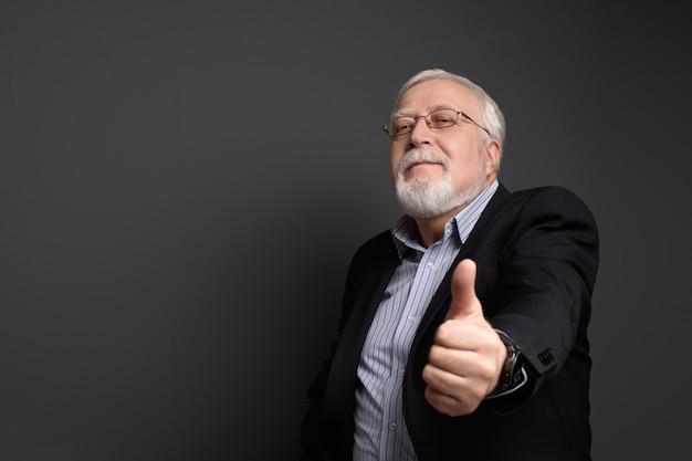 Affari, uomo brizzolato in occhiali sorride e mostra approvazione