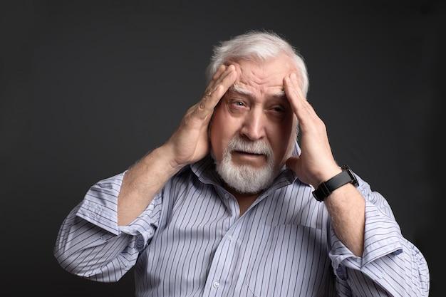 Affari, uomo dai capelli grigi che tiene la testa con due mani. mal di testa