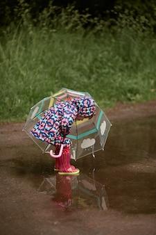 Affascinante bambina con l'ombrello si diverte in piedi in stivali di gomma in piscina dopo la pioggia