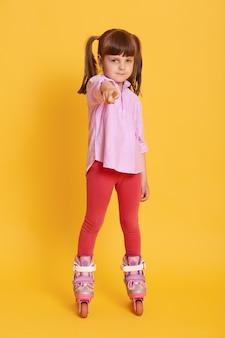 Affascinante bambino femmina in pattini a rotelle guardando e indicando la telecamera con il dito anteriore