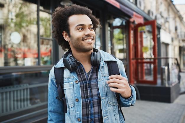 Affascinante bel maschio afro-americano con setola e taglio di capelli afro che osserva da parte mentre si tiene lo zaino e passeggiando in città.