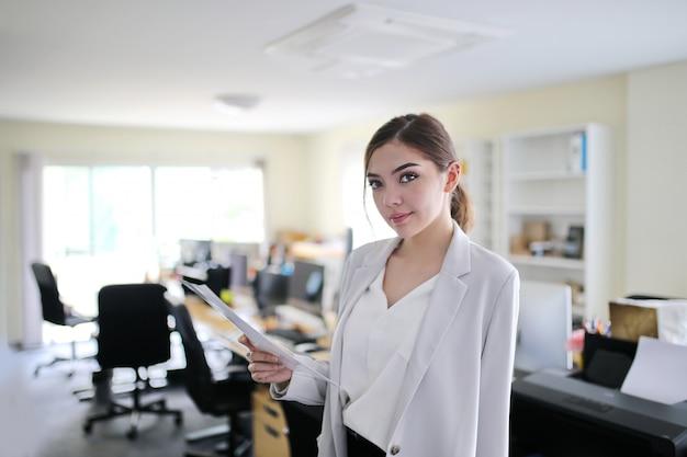 Affascinante bella abbronzatura della pelle asian smart smart donna lavoro a mano sul telefono portatile