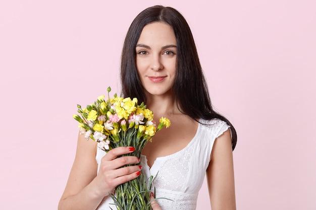 Affascinante bella donna tiene fiori rosa gialli con una mano, guardando direttamente la fotocamera, si sente soddisfatto.