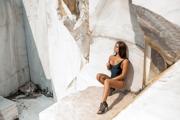 Affascinante bruna vestita in un costume da bagno nero e scarpe col tacco in posa in rocce bianche