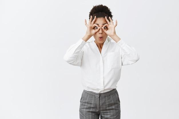 Affascinante collega spensierata e infantile in camicia bianca e pantaloni che fa cerchi con le mani sugli occhi, piegando le labbra come se guardasse attraverso il binocolo qualcosa di incredibile e sorprendente