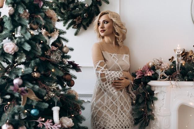 Affascinante donna bionda in abito bianco si pone in una stanza con grande albero di natale