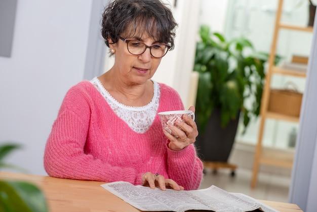 Affascinante donna senior vestita con un maglione rosa, leggendo il giornale