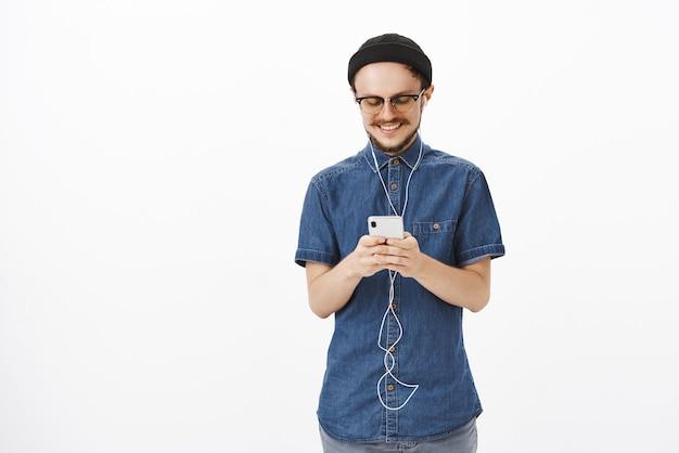 Affascinante e gioioso bel ragazzo adulto in berretto e occhiali con messaggi di barba durante il viaggio in metropolitana che tiene smartphone ascoltando musica in auricolari, soddisfatto con una simpatica nota romantica