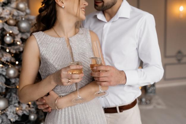 Affascinante giovane coppia in abiti fantasia posa con bicchieri di champagne prima di un albero di natale