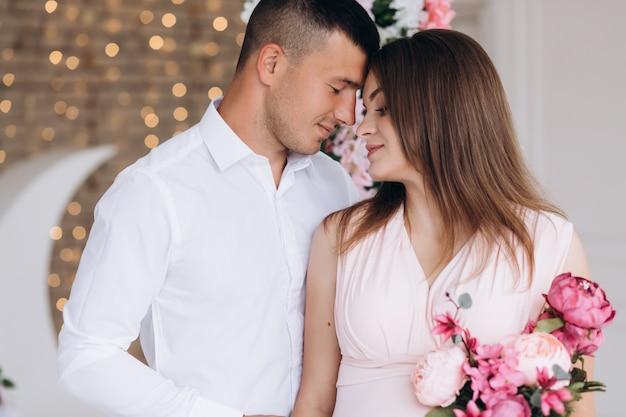 Affascinante giovane coppia in attesa pone in uno studio bianco ricco decorato con fiori rosa