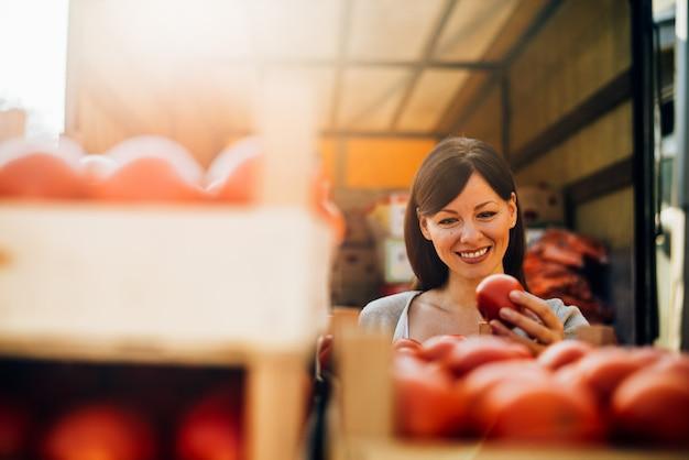 Affascinante giovane donna acquistare pomodori.