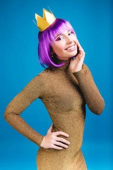 Affascinante giovane donna alla moda in abito di lusso dorato sorridente. taglia i capelli viola, corona, sorriso amichevole, espressione di positività, felicità, celebrazione del carnevale, festa.