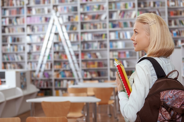 Affascinante giovane donna in biblioteca o libreria