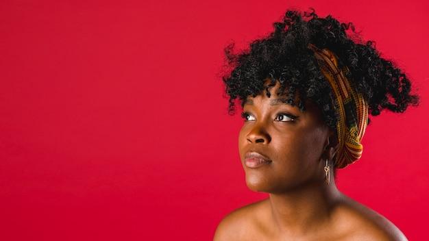 Affascinante giovane donna nera nuda su sfondo colorato