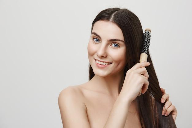 Affascinante giovane donna spazzolatura dei capelli e sorridente
