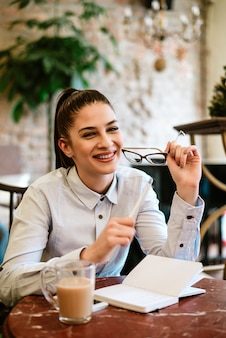 Affascinante giovane giornalista seduto al caffè. guardando la fotocamera