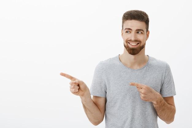 Affascinante giovane maschio soddisfatto e felice con barba e baffi sorridente deliziato con denti bianchi perfetti che punta e che guarda a sinistra soddisfatto e divertito sul muro bianco