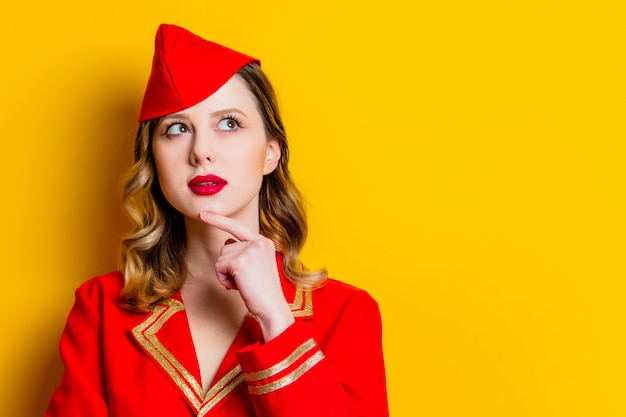 Affascinante hostess vintage che indossa in divisa rossa