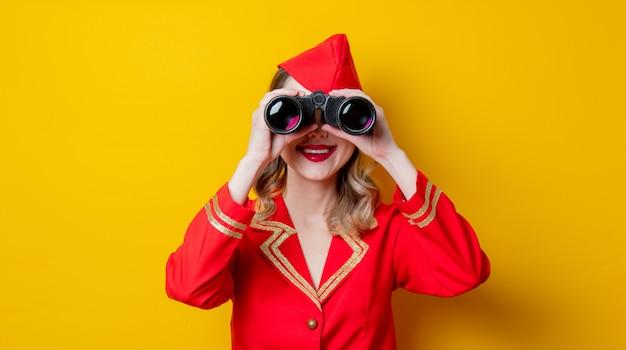 Affascinante hostess vintage che indossa in uniforme rossa con binocolo