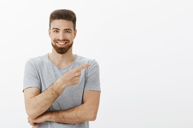 Affascinante imprenditore indipendente di bell'aspetto con barba e acconciatura alla moda in maglietta grigia che punta proprio verso lo spazio della copia e sorridente assicurato e felice di parlare alla gente dell'ottimo prodotto