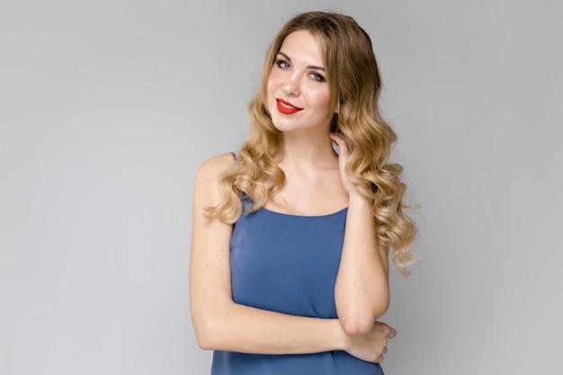 Affascinante ragazza con i capelli lunghi ricci bianchi ragazza in un blu in alto
