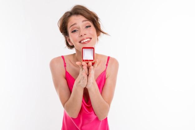 Affascinante ragazza europea in un abito rosa con una scatola con un anello nuziale su un muro bianco
