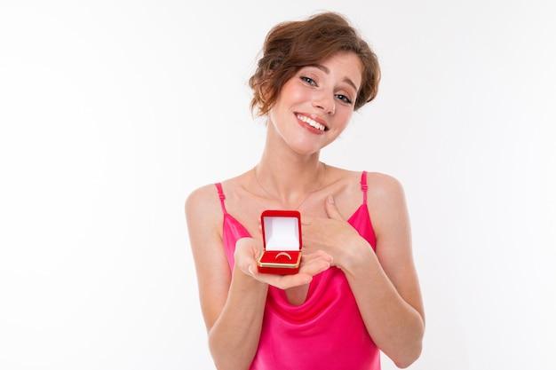 Affascinante ragazza europea in un abito rosa con una scatola rossa con una fede nuziale su un muro bianco