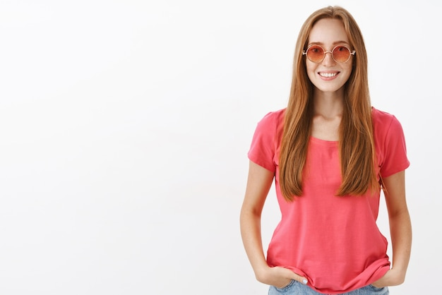 Affascinante ragazza hippie dall'aspetto amichevole con i capelli rossi e le lentiggini che si tengono per mano in tasca e sorridono casualmente indossando occhiali da sole rosa alla moda e camicetta sopra il muro bianco