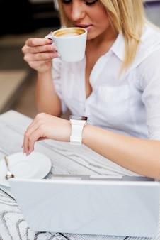 Affascinante ragazza imprenditore elegante utilizzando l'orologio moderno mentre beve un caffè.