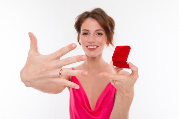 Affascinante ragazza in un abito rosa messo su un anello nuziale su un muro bianco