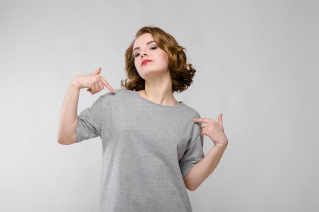 Affascinante ragazza in una maglietta grigia su un grigio