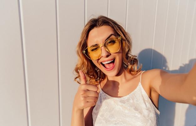Affascinante ragazza sorridente in occhiali gialli ammiccanti e mostrando un pollice in su