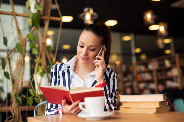 Affascinante ragazza sta parlando sul cellulare mentre si tiene un libro.