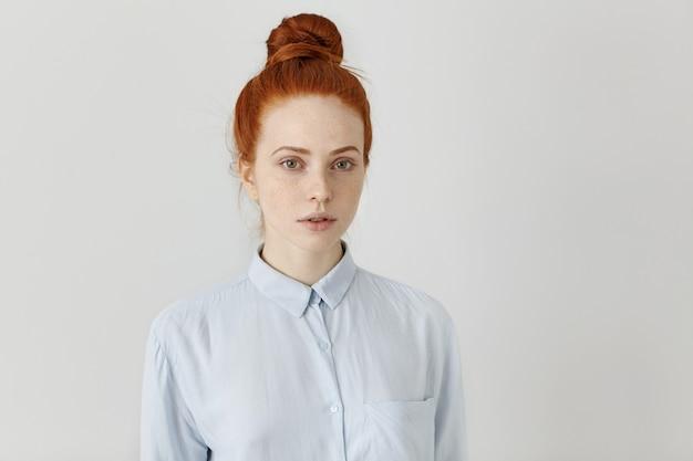 Affascinante ragazza studentessa con nodo di capelli allo zenzero che indossa camicia formale