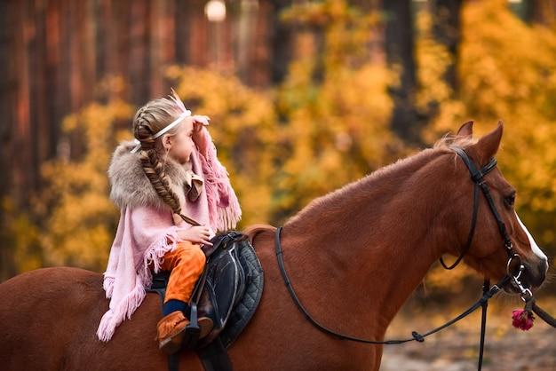 Affascinante ragazzina vestita da principessa cavalca un cavallo intorno alla foresta autunnale