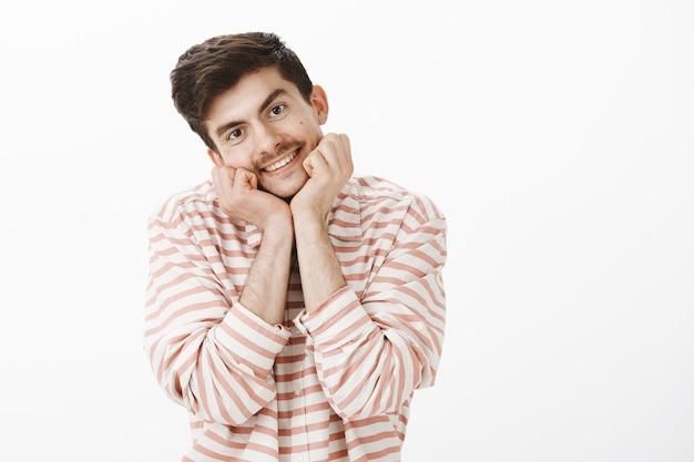 Affascinante ragazzo carino con baffi, testa appoggiata sulle mani e sorridente amichevole, guardando con ammirazione, ascoltando attentamente il discorso di un docente attraente, in piedi sopra il muro grigio