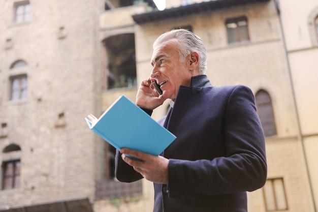 Affascinante uomo d'affari parlando su uno smartphone
