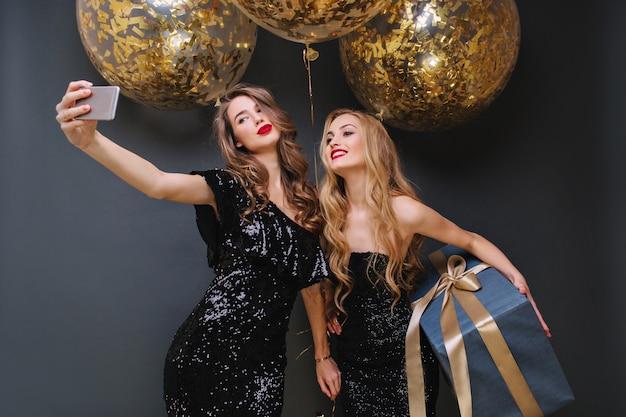 Affascinanti giovani donne alla moda in abiti neri di lusso che fanno selfie con grandi palloncini con orpelli dorati. divertirsi, regalare, esprimere positività, sorridere.