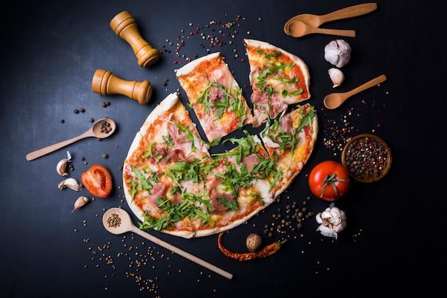 Affetta la pizza italiana con utensili e ingredienti sopra il piano di lavoro nero della cucina