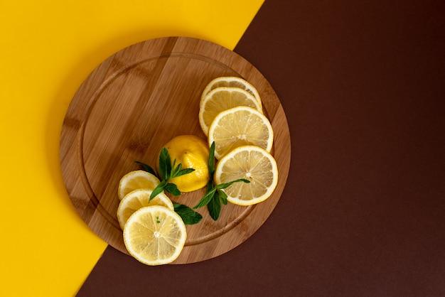 Affettati i limoni gialli su una tavola di legno marrone, accanto ad essa si trova un mucchio di menta verde, bevande estive