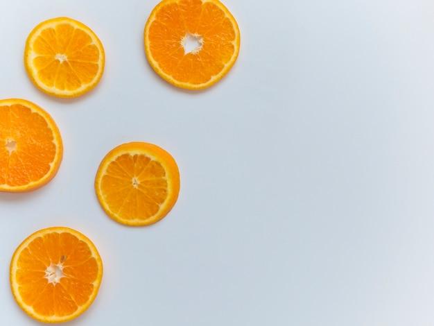 Affettato arancione su sfondo bianco e disposti sulla dimensione della mano sinistra del telaio