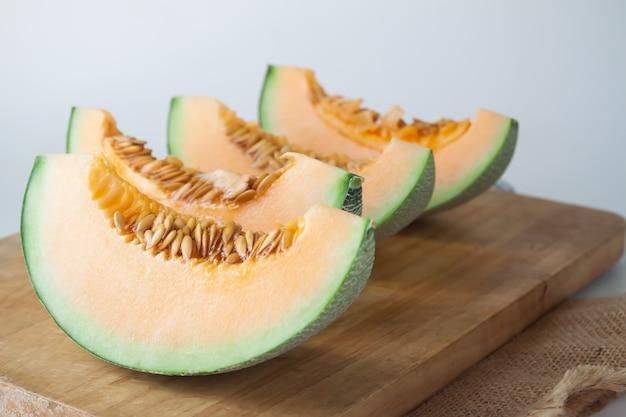 Affettato melone giapponese fresco, melone arancione sul tagliere. messa a fuoco selettiva
