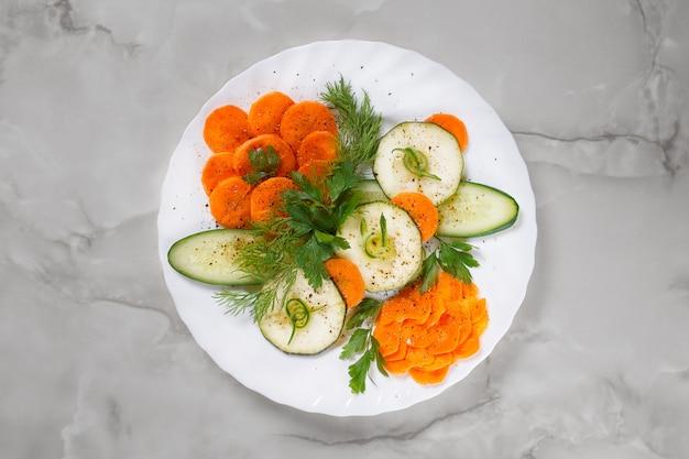 Affettatura festiva di verdure fresche con prezzemolo e aneto su un piatto bianco su uno sfondo di marmo grigio.
