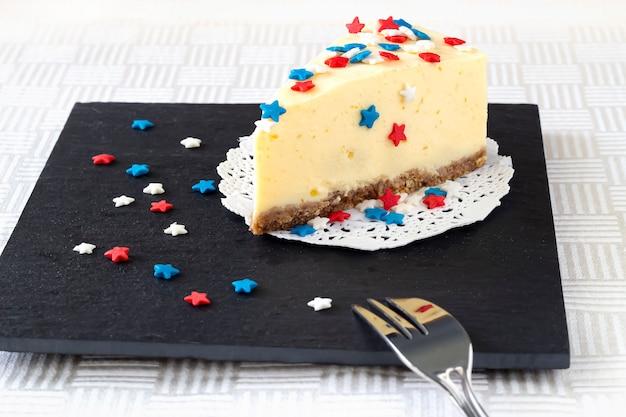 Affetti la cheesecake normale di new york sul bordo dell'ardesia.