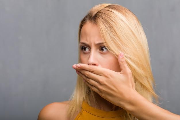 Affronti il primo piano, ritratto di una bocca della copertura della giovane donna bionda naturale