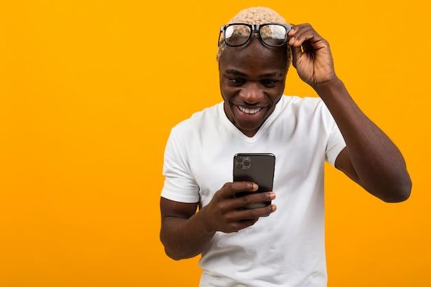 Africano bello dalla pelle scura in vetri con vista difficile che sorride sorridendo guardando il telefono su un fondo giallo